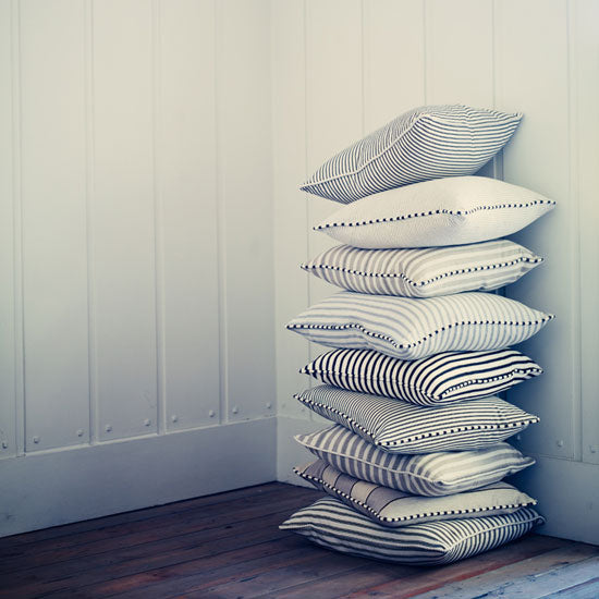 A stack of striped cushions in the corner of the room