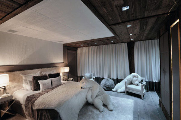 dark brown and white double bedroom with two large stuffed polar bear toys in the room