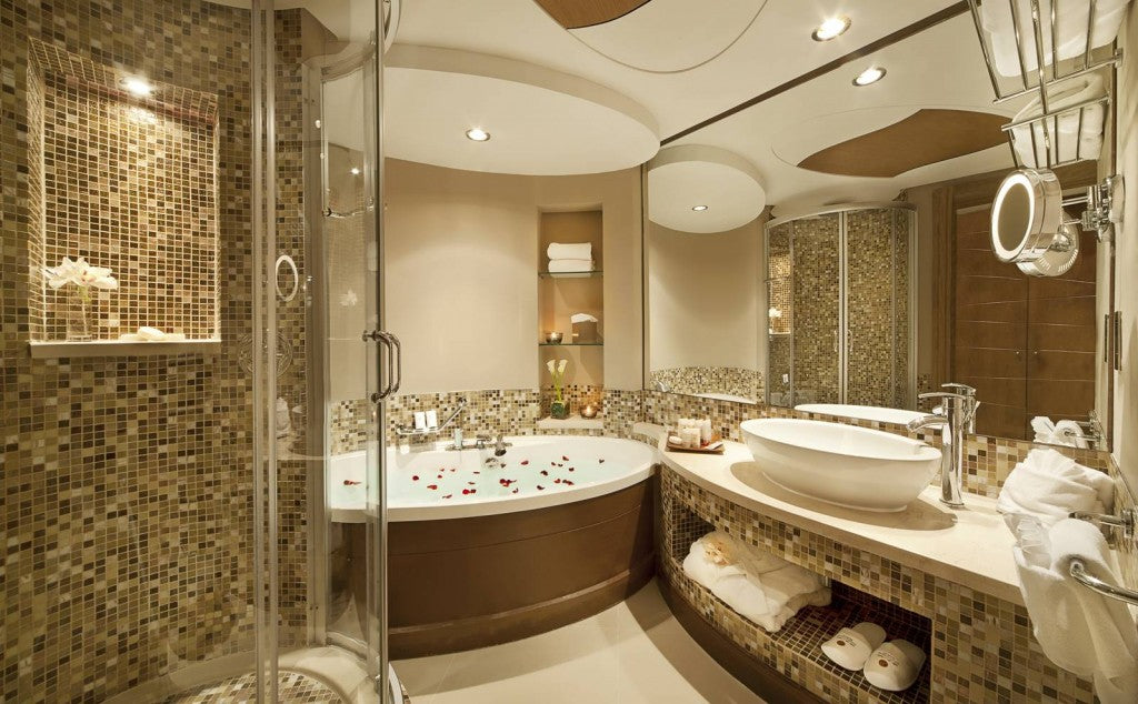 Small brown and beige tiles throughout a cream bathroom with oval based shower and oval bathtub