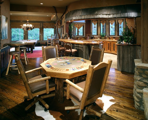 Poker table in a wooden cabin, with pool table and kitchen bar in the background