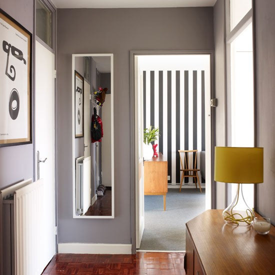 A grey hall with mirror on one wall, looking into a black and white striped room