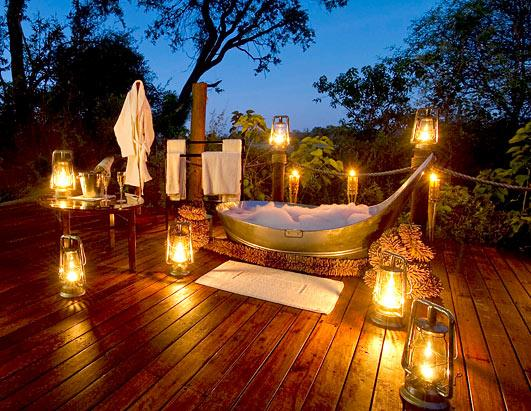 Luxury metal bathtub outside on a wooden deck, surrounded by lanterns