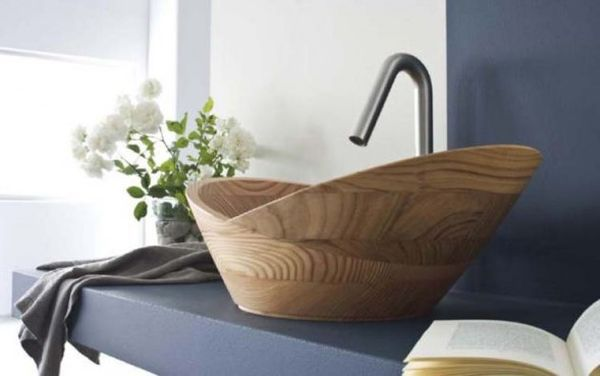 Wooden sink bowl sitting on a dark blue counter, with matching dark blue wall behind and white wall to the left