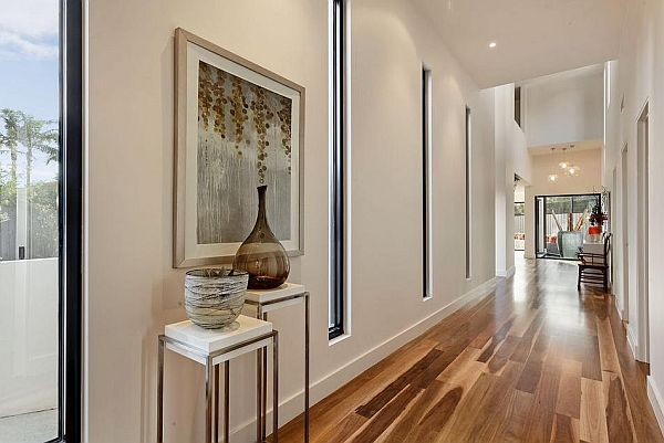 Wide corridor with dark wood flooring, white walls and tall slit windows leading into the rest of the house
