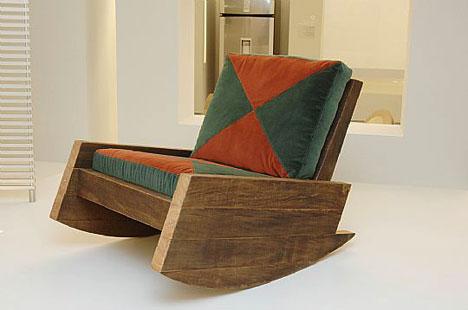 Modern dark wood rocking chair with green and red diamond patterned pads