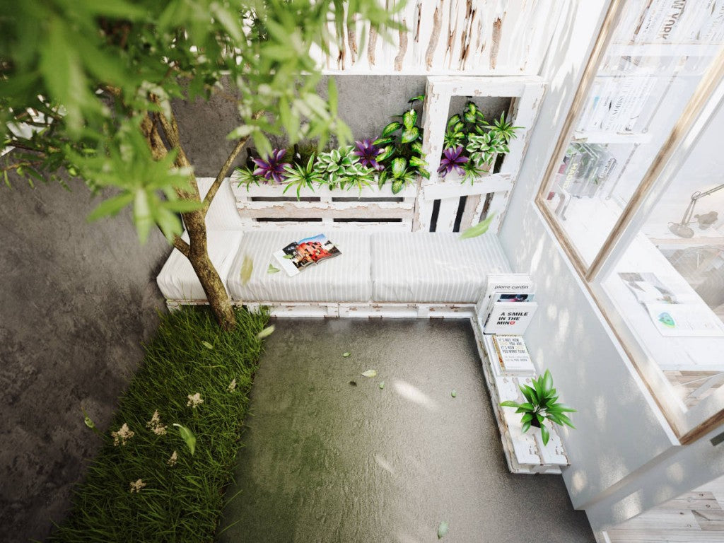 Looking down at a rustic white garden bench in a cosy alcove of a concrete courtyard
