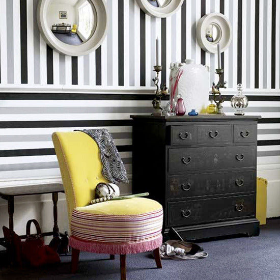 White, black and grey striped wallpaper with round mirrors on the wall and a black set of drawers