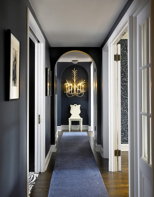 Dark blue and white hallway with long blue rug from one end to the other