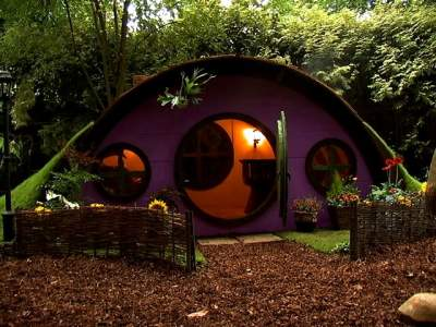 A outdoor pod room with purple exterior and curved roof