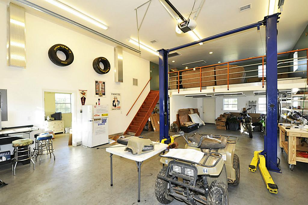 Large white garage workshop with a mezzanine containing a sofa