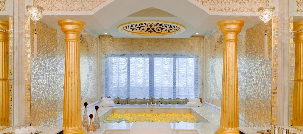 Very bright cream and orange bathroom, with two pillars decorating the entrance to a bath tub