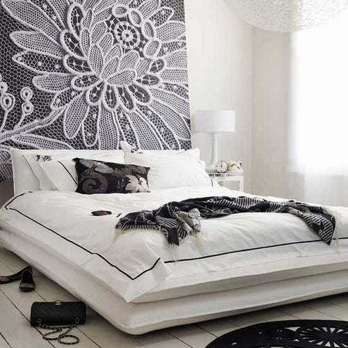 Black and white large wall art behind a white bed, depicting a flower head using macrame cord