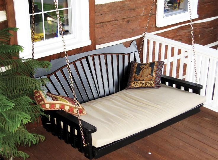A wooden black double swing chair on a front porch, with teddy cushions