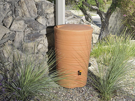 A terracotta pot with a lid placed in the garden