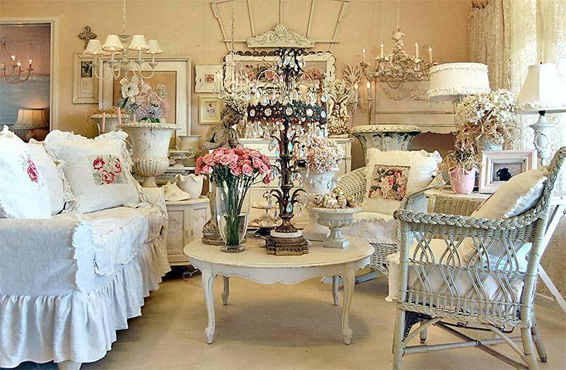 White wicker furniture in a living room with white round coffee table and touches of pink used to accessorize the room