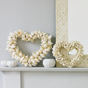 Two Cream Hearts Made From Shells, Positioned On A Fireplace