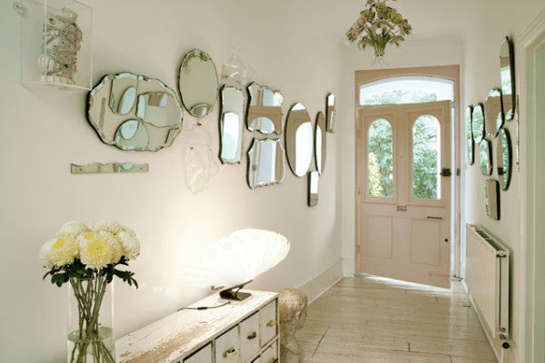 Cream front hallway with tiled floors and many mirrors on the wall