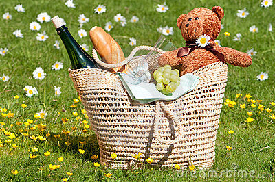 A woven shoulder bag containing a green corked bottle, baguette and teddy bear
