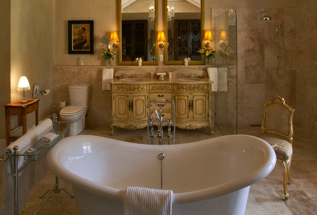 Luxurious cream bathroom with cream and gold distressed looking cabinet and white fixtures
