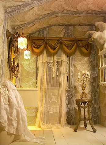 Lots of sheer fabric draped onto walls in a cream, beige and gold live space