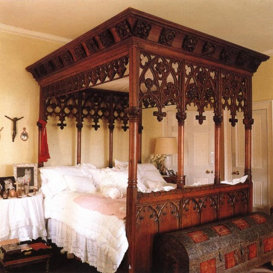 Dark wood four poster bed with intricately carved arch and rose pattern, with traditional trunk storage at the foot of the bed