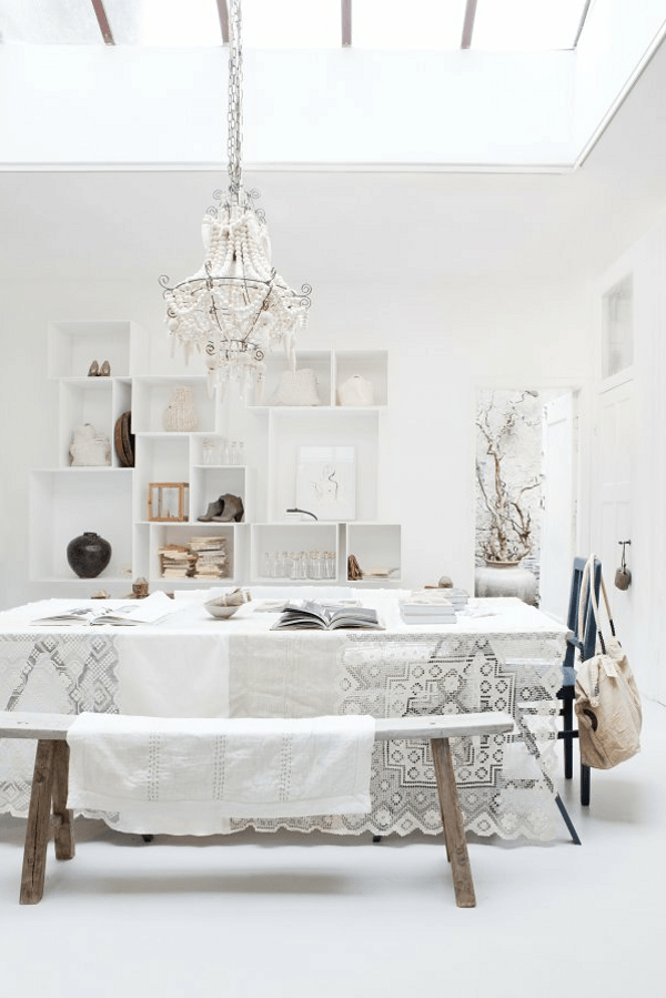 An all white dining room with lace dining table, with intricate pattern