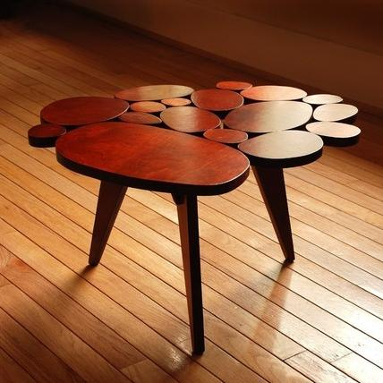 A small wooden side table with a top that is a collection of oval wooden blocks grouped together