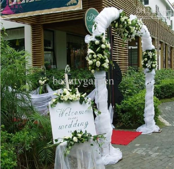 A voile fabric arch with white roses, creating the entrance of a wedding reception
