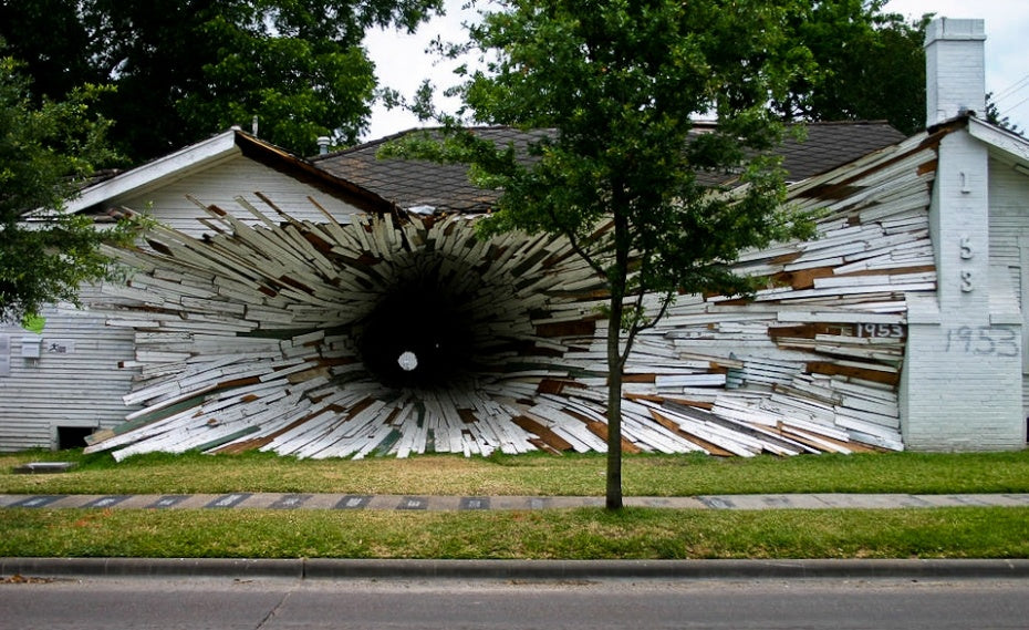 A wood panel house that looks like a black hole has devoured the side of the house