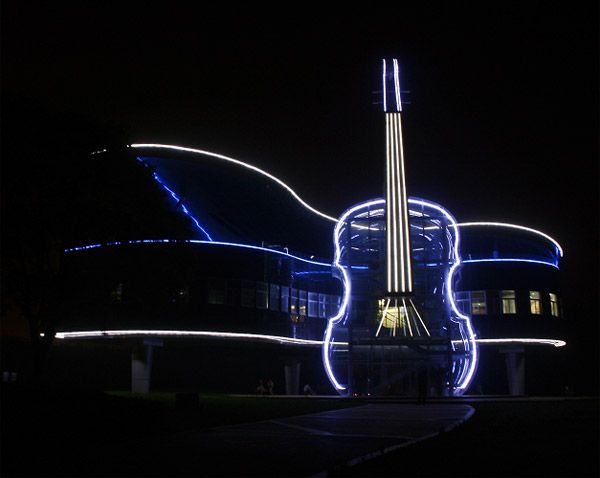 A building at night with halogen lighting on the rim of each floor and an outline of a guitar