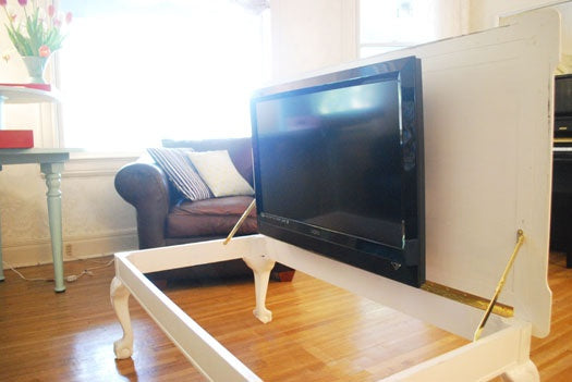 A TV mounted to the underside of a coffee table, accessible via hinged lid