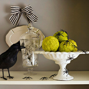 A decoarive raven on a mantel piece, as well as glass of skulls and spiders over mouldy apples
