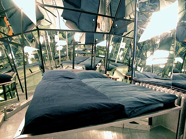 Two single beds on a suspended platform inside a room that has mirrors over all walls and surfaces