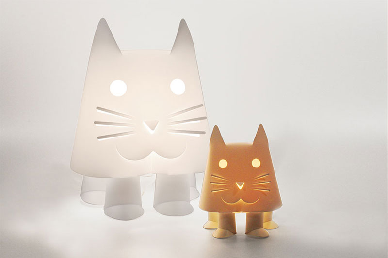 A kids nightlight in the shape of a cat, one large and white, the other smaller and orange