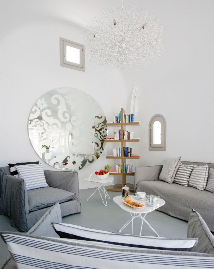 White living room with grey sofa and chairs and large round mirror with decorative design