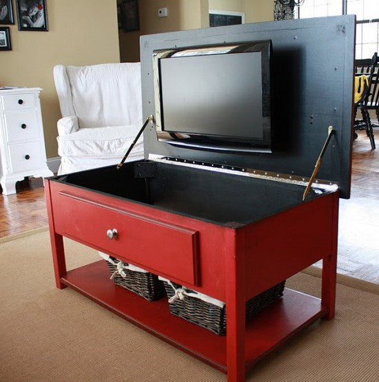A coffee side table with hinged lid, and a TV is mounted underneath the lid