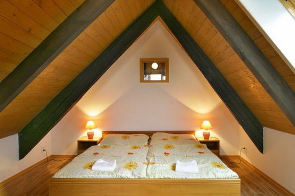 A loft space with stained wooden beam and light wooden roof panels, then a white double bed with bedside tables and lamps