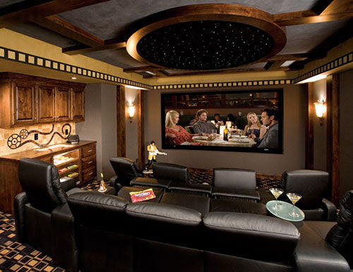 Luxury cinema room with leather recliner chairs and a large TV playing the film knocked up