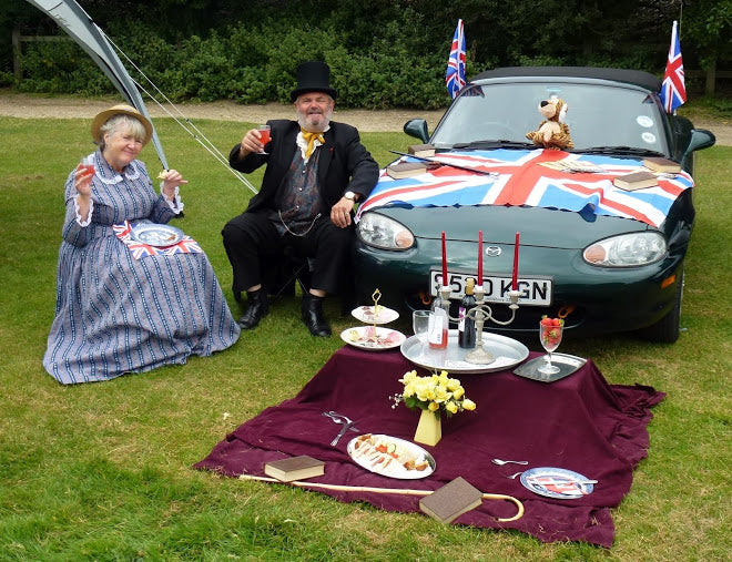 Older couple sat by a green Mazda adorned in a Union flag having a picnic