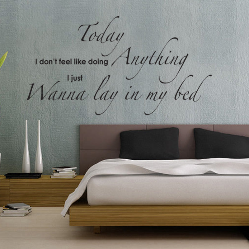 Cream bedding on a light wooden bed, with brown padded headboard and quote decal on the grey wall