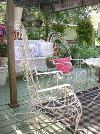 White intricate metal chairs on dull grey decking, under a  outdoor veranda