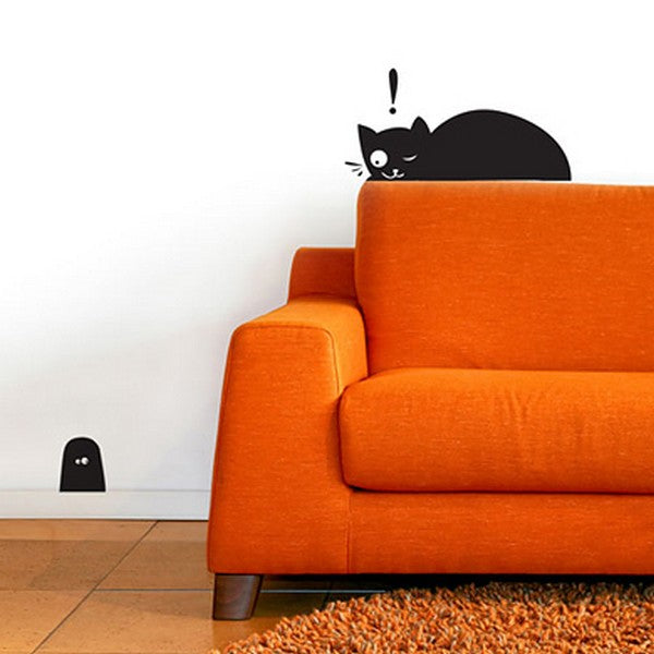 Orange sofa with black wall decal above it of a cartoon cat, looking down at a decal of a black mouse hole