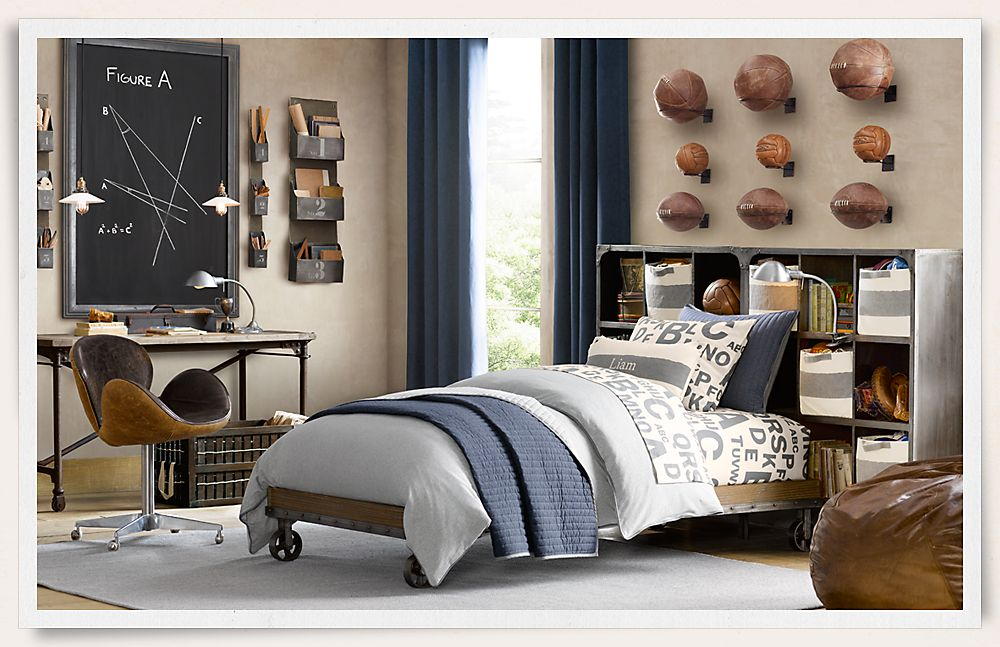 Sports themed bedroom with light blue, dark blue and grey bedding, and different types of sports balls mounted on the wall