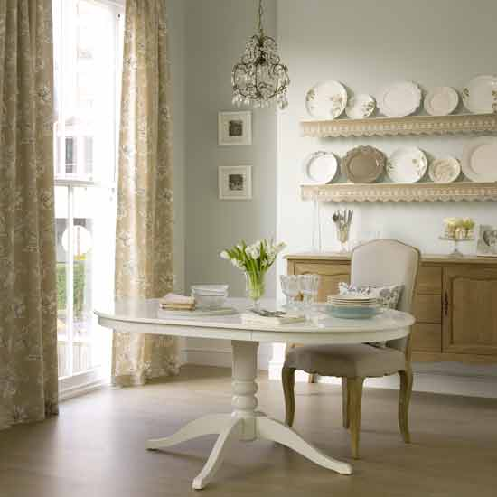 Cream, very light blue and gold dining room with gold curtains and plates hanging on the wall