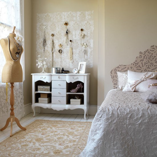 White and gold cream bedroom with feminine touches, such as clothes mannequin and dressing table