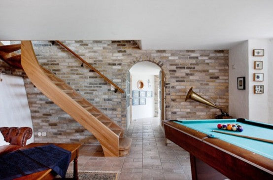 Basement games room with pool table and exposed brick walls and natural floor tiles