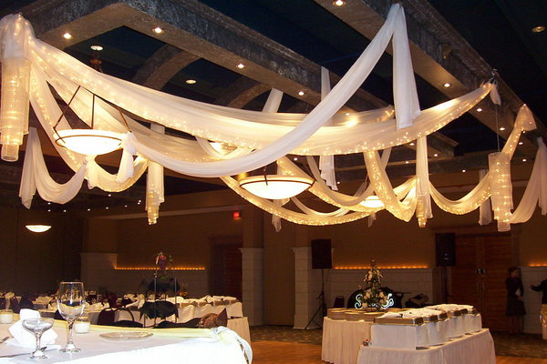 Draped canopies and voiles hanging from wood beams with fairy lights, looks like a wedding reception
