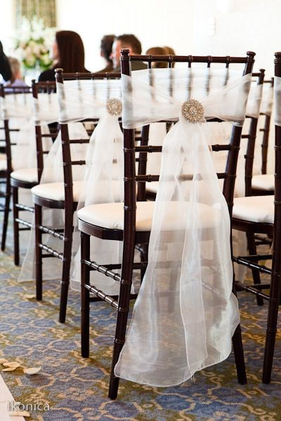 White voiles used on the back of chairs at a wedding ceremony