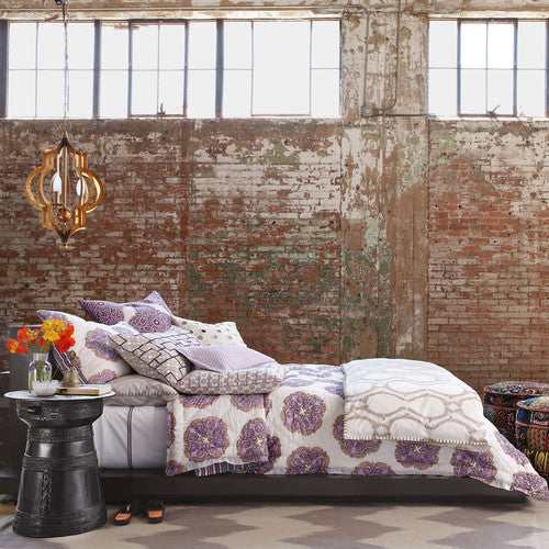 Industrial Brickwork Modernised Into A Funky Bedroom, With Purple And White Bedding