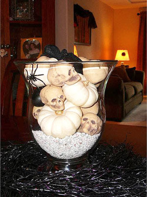White skulls and black spiders in a glass jar